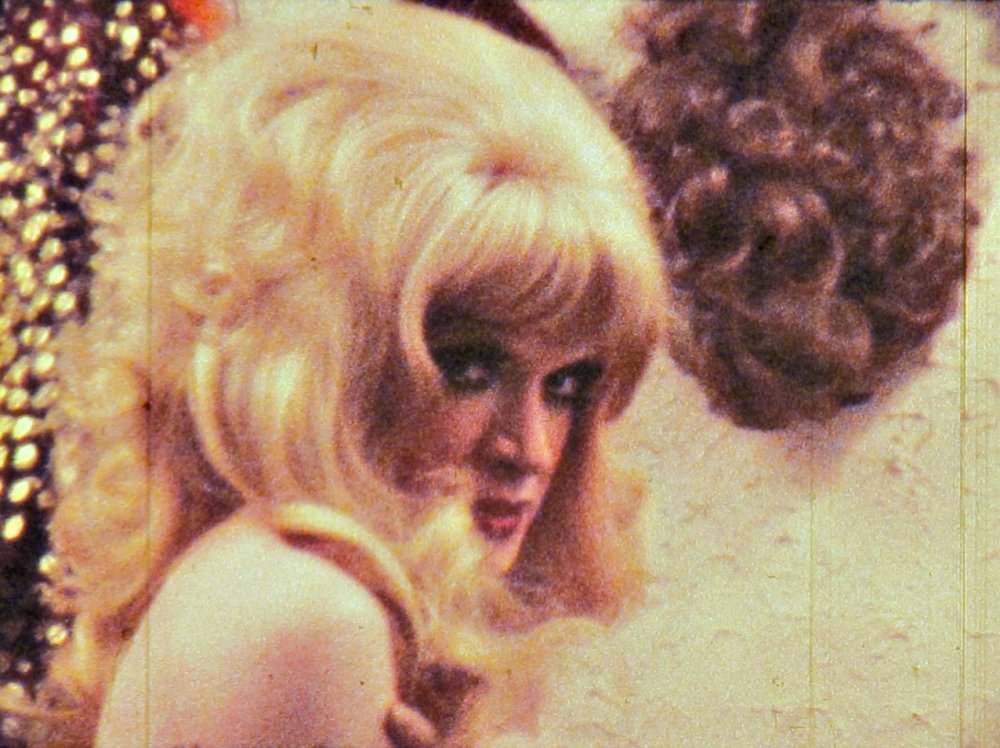 vanessa-1974-001-woman-in-blonde-wig-turning-to-camera